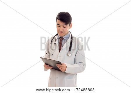 a young doctor in a white lab coat with a stethoscope and looking at Tablet isolated on white