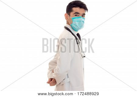 doctor in a white lab coat stands sideways with a mask on his face isolated on white