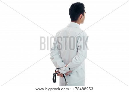 doctor in white gown stands looking backwards and holding a stethoscope isolated on white