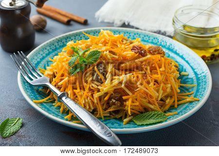 Vegetarian salad with pumpkin apples and raisins on a dark background. Selective focus.