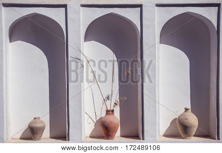 An Arched Niche In A White Wall With Old Clay Vases. Old Aged Plastered Faux Arch False Fake Window