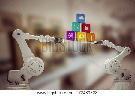 Digitally generated image of metallic robotic hands holding computer icons against factory