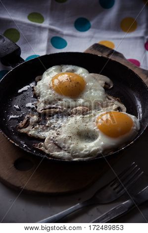 Two Fried Eggs With Mushrooms In A Pan