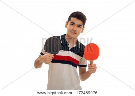 young guy stands up straight and holding rackets for table tennis is isolated on a white