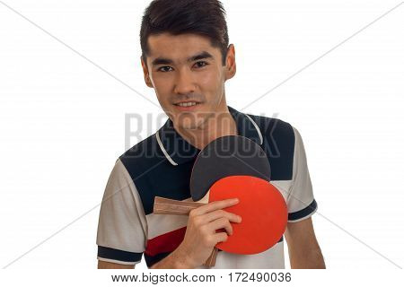 a young man holds in his hand rackets for table tennis and a close-up of a smiling isolated on white