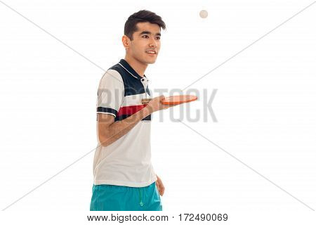 a young guy in a bright t-shirt stands sideways and holding a tennis racket isolated on white