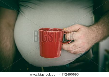 Red tea cup in man's hand close-up