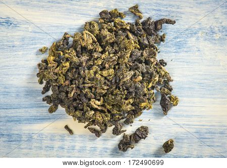 Green Chinese oolong tea. Close-up. Blue wood background.