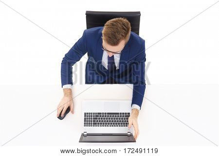 Overhead view of a handsome businessman working in office on a laptop. Business and office concept.