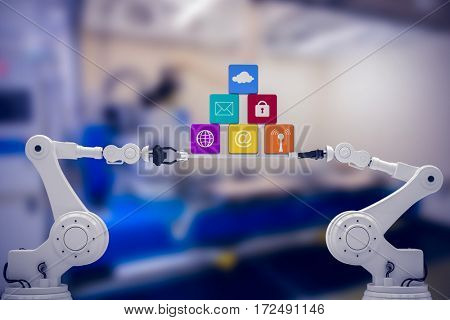 Digitally composite image of robotic hands holding computer icons against factory
