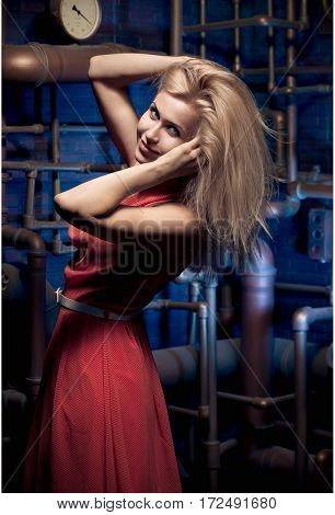 blonde in a red dress posing on a background of water pipes