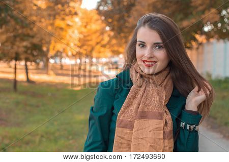 pin-up girl in a Brown scarf stands in the Park and smiles