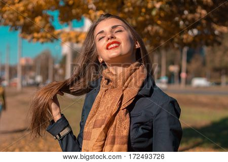 girl with a scarf keeps hair hand and lifted her head to the Sun