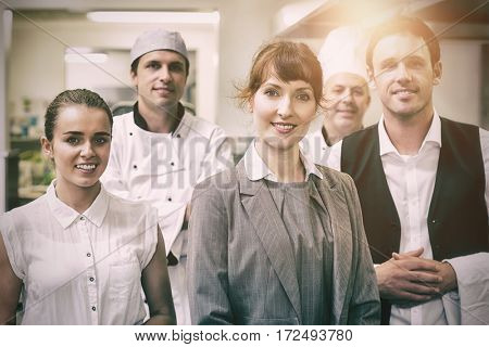Portrait of young female manager posing in modern kitchen with staff