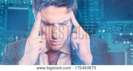 Tensed businessman suffering from headache against shining blue circuit board