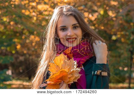 beautiful smiling girl standing on the street with leaves