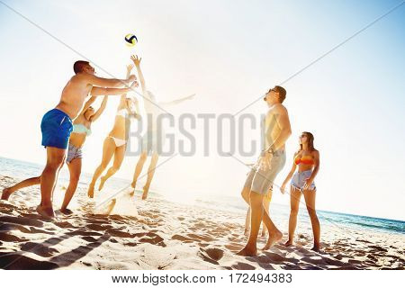 Group of friends is playing beach voleyball at sunset time
