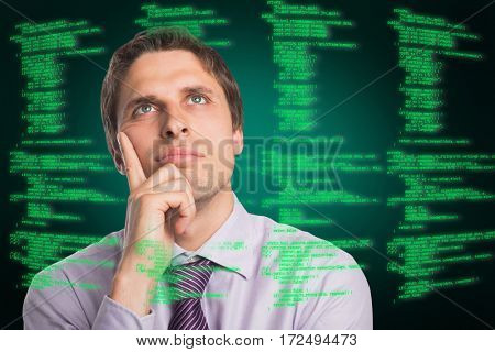 Close-up of thoughtful businessman looking up against green background with vignette