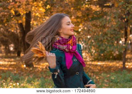 girl stands in the Park near trees and her hair fly through the air