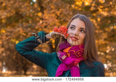 girl stands in the park looks away and holds a sprig of Rowan in his hand