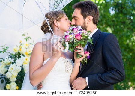 Bridal couple embracing each other in summer garden