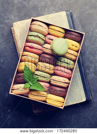 Colorful macaroons in a gift box over book on stone table. Sweet macarons. Top view. Retro toned