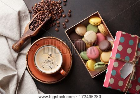 Coffee cup, beans, chocolate, macaroons gift box on old kitchen table. Top view