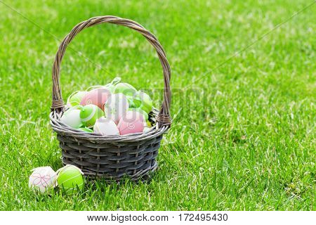Easter eggs basket on grass. View with copy space
