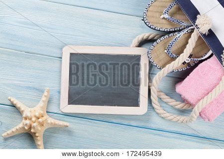 Beach accessories. Bag with flip-flops and towel and blackboard for your text on wooden background. Top view with copy space