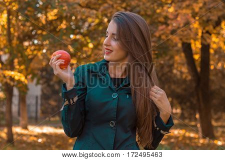 girl stands on the street looks to the side and holding a Apple