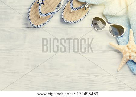 Beach accessories. Towel, flip-flops, starfish and sunglasses on wooden background. Top view with copy space. Sunny toned