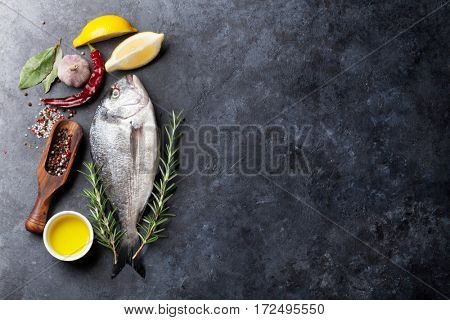 Raw fish cooking and ingredients. Dorado, lemon, herbs and spices. Top view with copy space on stone table