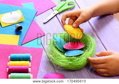 Small child does Easter decor. Child holds a felt egg in hand. Colorful felt Easter eggs and sisal nest, sewing tools and materials on a table. Simple and creative Easter decor idea