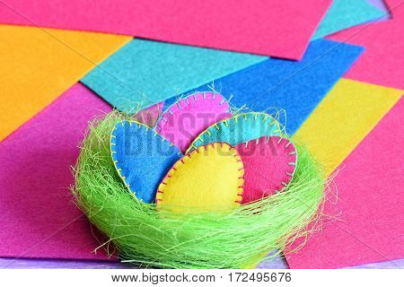 Easter eggs in a nest decor. Felt Easter eggs set in a green sisal nest on multi-colored felt sheets. Bright paschal background. Closeup
