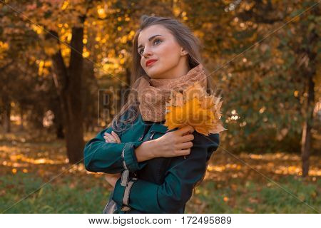 beautiful girl stands on the street looks Afar and keeps the leaves