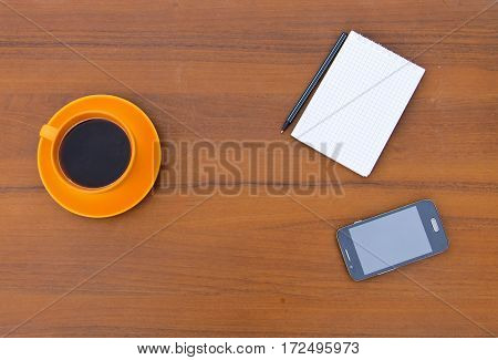 Coffee cup with smartphone notepad and pen on the wooden desk