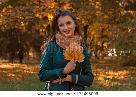 girl standing on the street looks straight and keeps the dry leaves