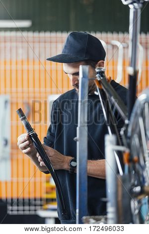 Young man in black cap holding metal bar