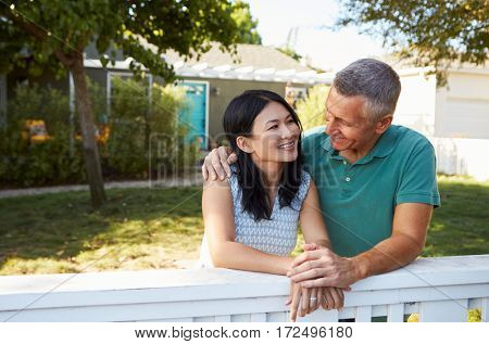Mature Couple Leaning On Back Yard Fence