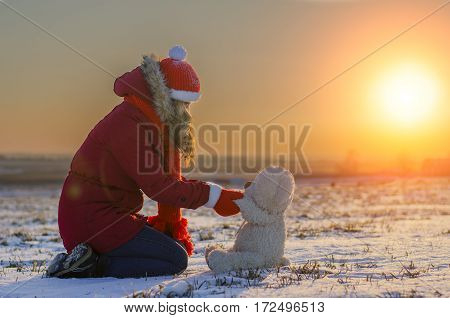 young girl in a red and a teddy bear at sunset