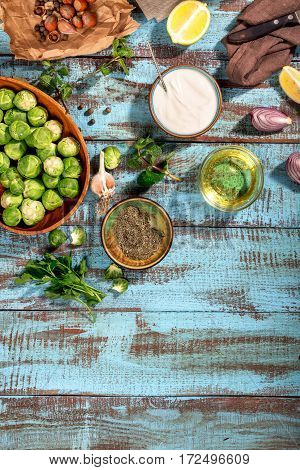 Healthy food. Raw brussels sprouts with different ingredients for cooking healthy food on wooden table with copy space top view
