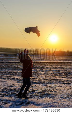 Girl throws a soft toy at sunset