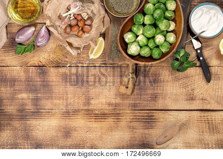 Brussels sprouts with ingredients for cooking tasty and healthy food on wooden table with border top view. Healthy food