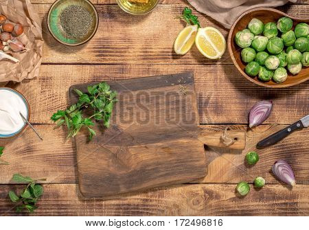 Around the wooden cutting board brussels sprouts and ingredients for cooking healthy and delicious food on a wooden table top view. Healthy food