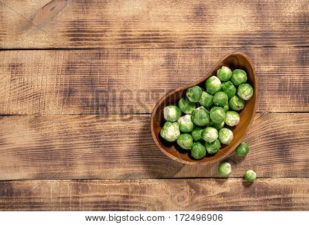 Brussels sprouts in a wooden bowl on wooden table with copy space top view. Healthy food