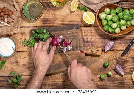 Man preparing healthy food on wooden table top view