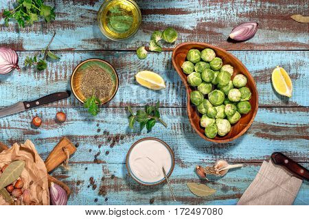 Raw brussels sprouts with ingredients for cooking tasty and healthy food on wooden table top view