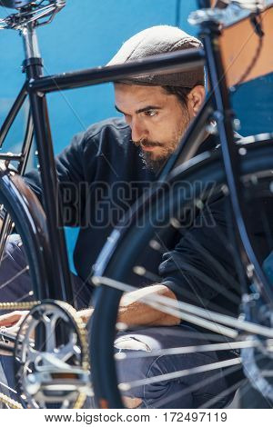 Close-up of bearded man taking measurements of bicycle