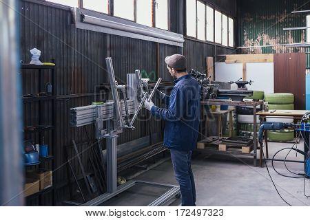 Unrecognizable man in cap working with metal details in workshop