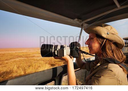 Woman taking photo with professional camera aboard safari jeep at African savannah